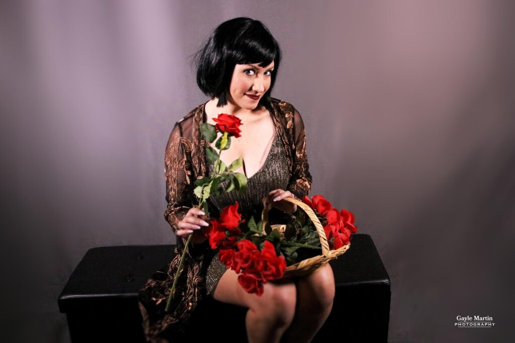 A studio portrait of a woman in 1920s attire holding a red rose.